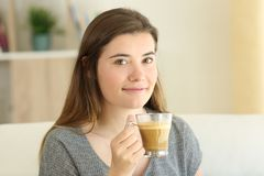 Happy teen holding a coffee with milk cup looking at you. Sitting on a couch in the living room at home Stock Photography