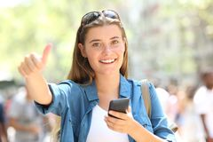 Happy teen holding phone gesturing thumb up royalty free stock photos