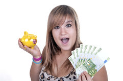 Happy teen holding a piggy bank and bills. Isolated on white background Royalty Free Stock Photography