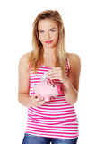 Happy teen holding a piggy bank and dollars. Stock Photography