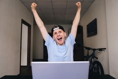 Happy teen with joy raised his hands up sitting at the computer in the house room. Happy teen with joy raised his hands up sitting at the computer in the house Royalty Free Stock Photos