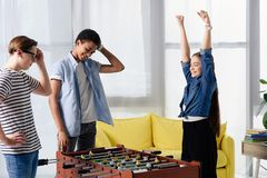 Happy teen kid winning table football at multicultural teenagers. At home royalty free stock images