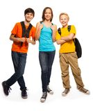 Happy teen kids with backpacks. Happy three teen kids with backpacks standing isolated on white Royalty Free Stock Photos
