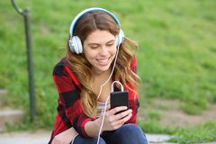 Happy teen listening to music checking phone in a park royalty free stock images