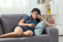 Happy teen listening to music with phone and headphones. Happy teen listening to music with a smart phone and headphones sitting on a couch in the living room at Stock Photo
