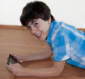 Happy Teen is Looking to the Digital Notepad Royalty Free Stock Photography