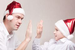 Happy teen and man in santa hat Royalty Free Stock Photography