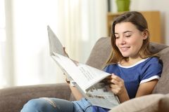 Teen reading a newspaper on a sofa at home. Happy teen reading a newspaper sitting on a sofa in the living room at home stock photo
