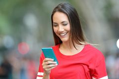 Teen in red using a blue smart phone on the street. Happy teen in red using a blue smart phone walking on the street royalty free stock photography