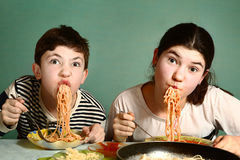 Happy teen siblings boy and girl eat spaghetti Royalty Free Stock Image