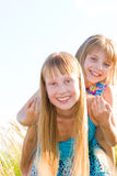 Happy teen sisters. On green summer meadow background Stock Images