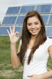 Happy teen with solar panels. Half body portrait of smiling female teenager gesturing OK sign with solar panels in background Royalty Free Stock Photography