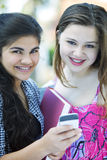 Happy teen students with phone. Happy teen students smiling with mobile phone Royalty Free Stock Images