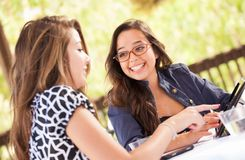 Happy Teen Students Using Their Computer Electron. Expressive Young Adult Girlfriends Using Their Computer Electronics Outdoors Stock Photography