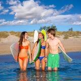 Happy teen surfers talking on beach shore Stock Photos