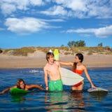 Happy teen surfers talking on beach shore Stock Photography