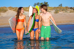 Happy teen surfers talking on beach shore Royalty Free Stock Image