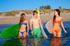 Happy teen surfers talking on beach shore Stock Photos