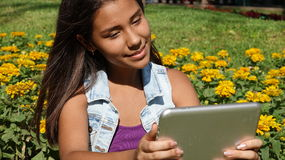 Happy Teen With Tablet Device. Stock photo of a teen girl Royalty Free Stock Photo