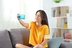 Happy teen taking selfies sitting on a couch. In the living room at home Royalty Free Stock Photography