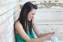 Happy Teen texting on cell phone stock photography