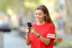 Happy teen texting on phone on the street Royalty Free Stock Image