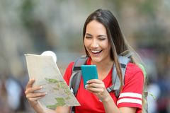 Teen tourist using a phone and holding a map royalty free stock image