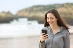 Happy teen uses a smart phone on the beach. Happy teen laughing using a smart phone walking on the beach Stock Photos
