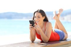 Happy teen using phone lying on a bench on the beach royalty free stock photos