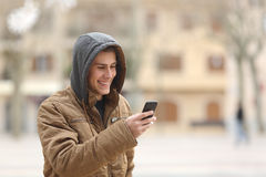 Happy teen walking and using a smart phone Royalty Free Stock Images