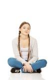 Happy teen woman sitting cross legged. Stock Photo