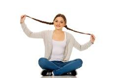 Happy teen woman sitting cross legged. Royalty Free Stock Photography