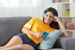 Happy teen in yellow listening to music at home. Happy teen in yellow listening to music sitting on a couch in the living room at home Stock Photo
