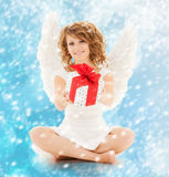 Happy teenage angel girl with christmas gift. Holidays, xmas and costumes concept - happy teenage angel girl with christmas gift Stock Image