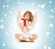Happy teenage angel girl with christmas gift. Holidays, xmas and costumes concept - happy teenage angel girl with christmas gift Stock Images