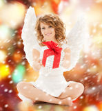 Happy teenage angel girl with christmas gift. Holidays, xmas and costumes concept - happy teenage angel girl with christmas gift Stock Photo