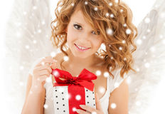 Happy teenage angel girl with christmas gift. Holidays, xmas and costumes concept - happy teenage angel girl with christmas gift Royalty Free Stock Photos