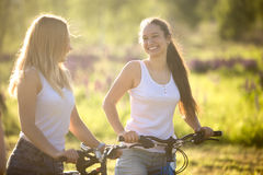 Happy teenage bicyclists girls. Two young beautiful cheerful women girlfriends wearing jeans shorts on bicycles in park on sunny summer day, having good time Royalty Free Stock Photos