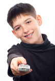 Happy teenage boy changing channels on television Stock Images