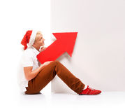 A happy teenage boy in a Christmas hat holding a red arrow Stock Images