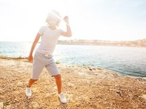 Happy teenage boy dancing on the beach in summer royalty free stock photography