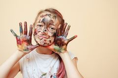 Playful boy being messy with colorful paints. Happy teenage boy with face and hands in colorful paints smiling at camera stock images