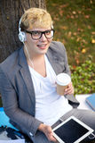 Happy teenage boy in headphones with tablet pc Royalty Free Stock Photos