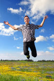 Happy Teenage Boy Jumping. On summer field background Royalty Free Stock Images