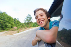 Happy teenage boy leaning out of a car window. Smiling happily as he enjoys the speed of the moving vehicle royalty free stock photos