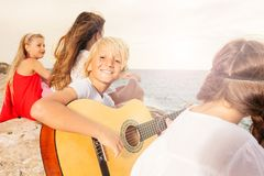 Happy teenage boy playing guitar on the beach. Portrait of happy teenage boy playing guitar to his friends on the beach royalty free stock photos