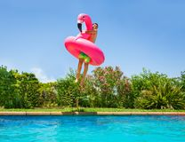 Happy teenage boy playing pool games in summer. Portrait of happy teenage boy with big inflatable flamingo swim toy jumping in outdoor swimming pool stock image