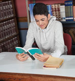 Happy Teenage Boy Reading Book At Table. Portrait of happy teenage boy reading book at table in library Royalty Free Stock Images