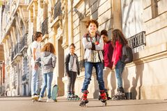 Happy teenage boy rollerblading with friends. Portrait of happy teenage boy rollerblading with friends at city sidewalks stock photo