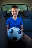 Happy teenage boy sitting with football in the back seat of car Stock Photos